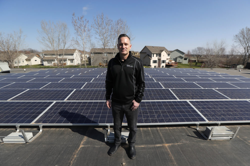 Todd Miller stands next to solar panels on the roof of his solar installation business in Ankeny, Iowa. For years wind and solar were friendly twins in the campaign for green alternatives to fossil fuels, but the relationship is getting ugly in a number of states, especially in Iowa, where more than 4,000 turbines generate 37% of the state's electricity, the second highest rate in the country. (Charlie Neibergall/AP)