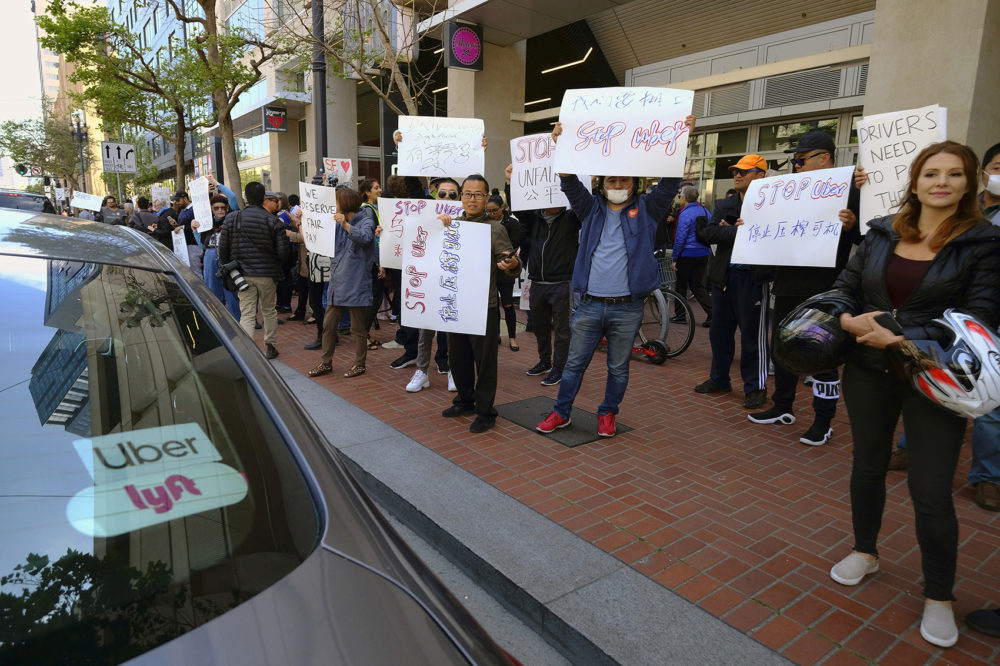 In this May 8, 2019,, file photo, Uber and Lyft drivers carry signs during a demonstration outside of Uber headquarters in San Francisco. Companies like Uber and Lyft helped create the so-called gig economy. (Eric Risberg, File/AP)