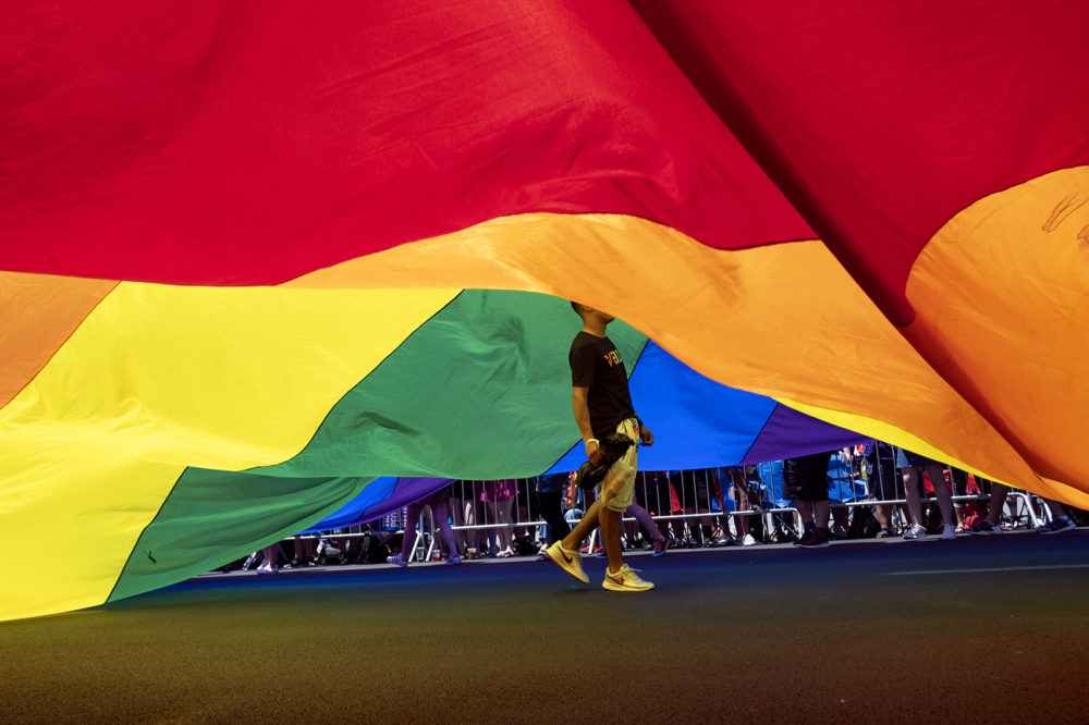 A participant walks under a large rainbow flag during the LBGTQ Pride march Sunday, June 30, 2019, in New York. (Craig Ruttle/AP)