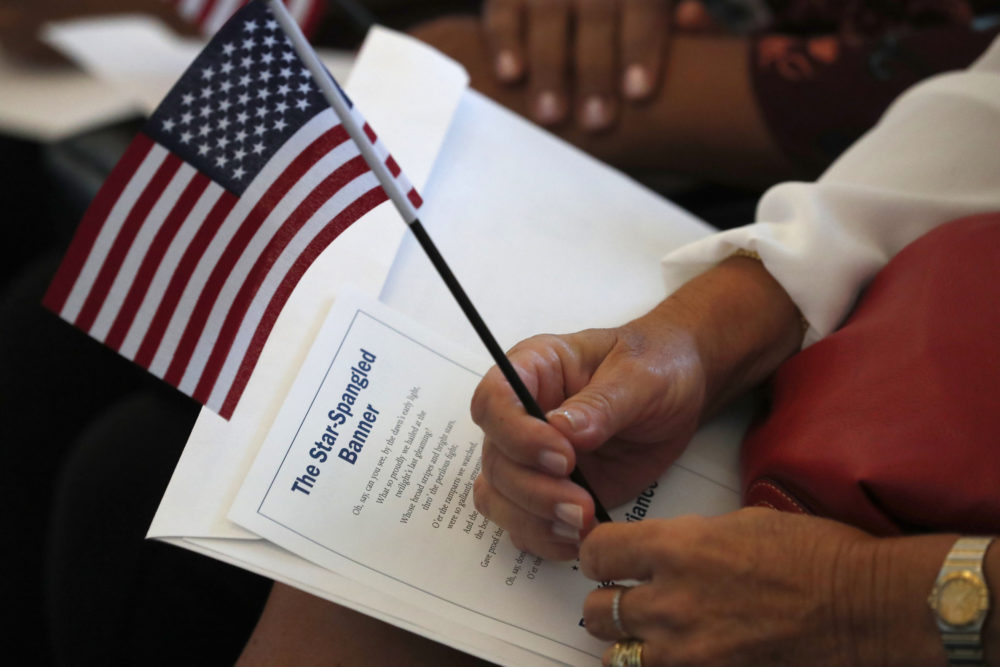 A citizen candidate holds an American flag and the words to The Star-Spangled Banner before the start of a naturalization ceremony at the U.S. Citizenship and Immigration Services Miami field office. (Wilfredo Lee/AP)
