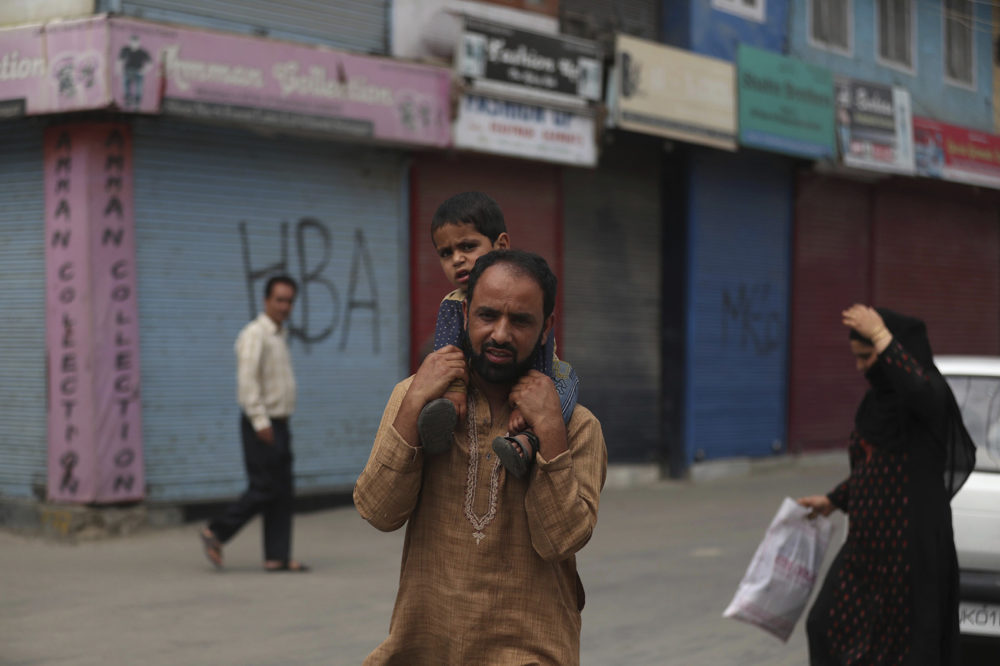 A Kashmiri man carries a child on his shoulders at a closed market area in Srinagar, Indian controlled Kashmir, Saturday, Aug. 31, 2019. New Delhi downgraded Muslim-majority Kashmir's autonomy on Aug. 5 and imposed a security clampdown to prevent any violent response. (AP Photo/Mukhtar Khan)