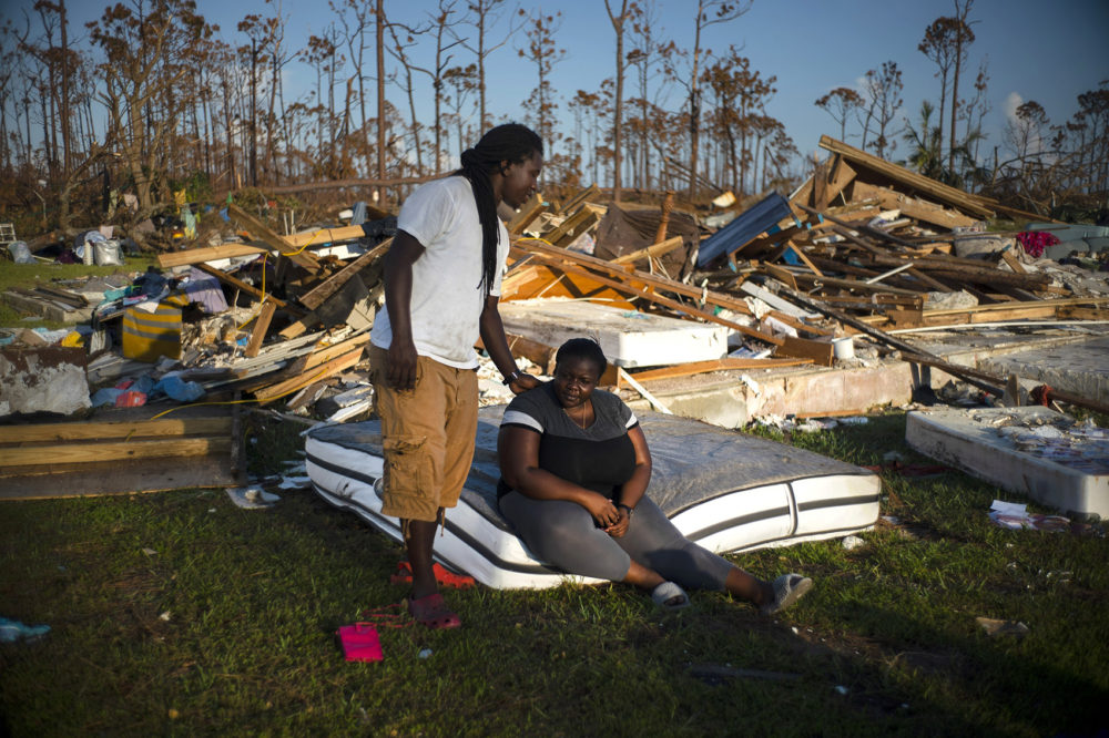Synobia Reckley pauses on a wet mattress as her husband Dexter Edwards consoles her amid the remains of their home destroyed by Hurricane Dorian in Rocky Creek East End, Grand Bahama, Bahamas, Sunday, Sept. 8, 2019. The couple married two days after Hurricane Mathew hit in 2016 but did not do serious damage. (Ramon Espinosa/AP)