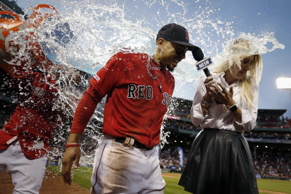 A teammate douses Boston Red Sox's Mookie Betts, center, after Betts scored a walkoff run during the ninth inning of a baseball game against the Baltimore Orioles in Boston, Sept. 29, 2019. (Michael Dwyer/AP)