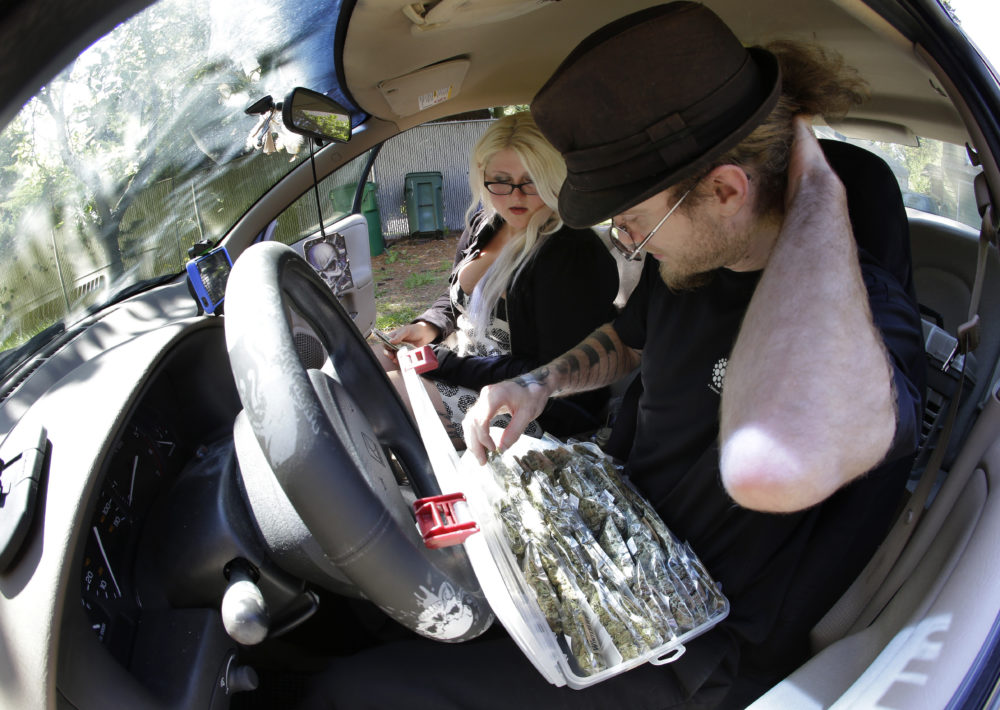 "Michael Kenworthy, right, a marijuana delivery driver, selects a package of pot for a customer who identified herself as ""Tracy,"" while conducting a transaction in Kenworthy's car outside Tracy's home in Seattle. (Ted S. Warren/AP)"