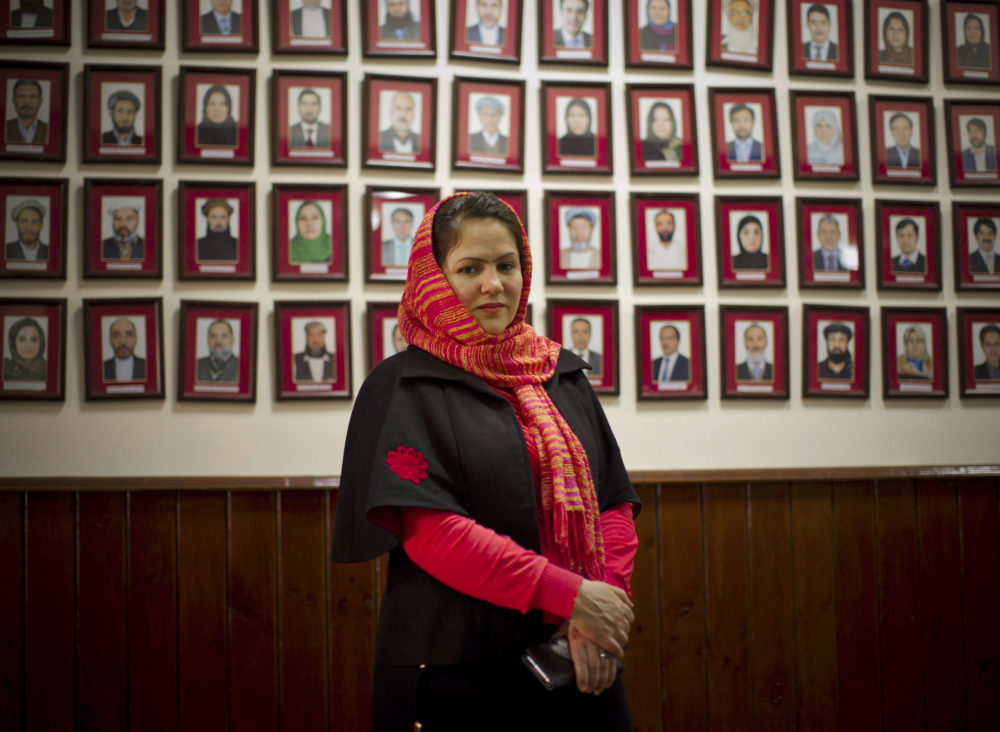 Afghan lawmaker Fawzia Koofi from Kabul poses next to a picture wall showing Afghanistan's 249 parliamentarians. (Anja Niedringhaus/AP)
