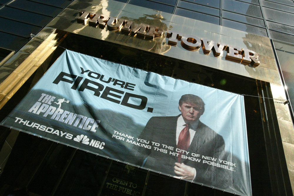 """A sign advertising the television show """"The Apprentice"""" hangs at Trump Towers April 15, 2004 in New York City.  (Peter Kramer/Getty Images)"""