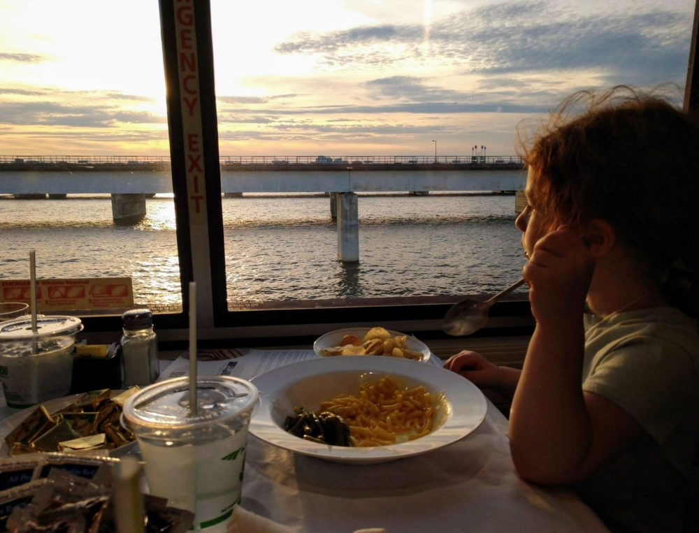 Transportation analyst Seth Kaplan's daughter enjoys macaroni and cheese with a view while riding in an Amtrak dining car. (Photo by Seth Kaplan/Here & Now)