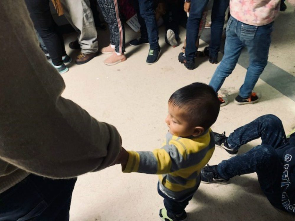 A little boy holds his father's hand at the Humanitarian Respite Center in McAllen, Texas.  The father and son are from Honduras. (Courtesy)