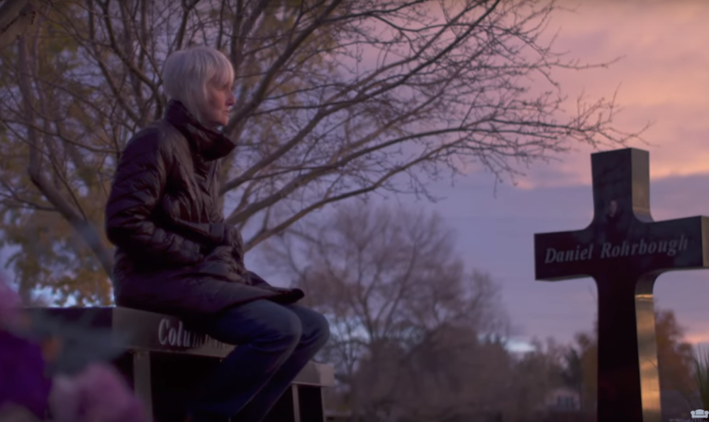 In this screenshot from American Tragedy, Sue Klebold sits at the memorial for the lives lost at Columbine.