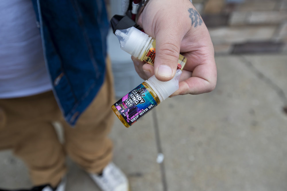 Dennis Yebba made the trip up to Salem, NH and holds three bottles of vaping juice just purchased at Smoker Cohoice including the cotton candy flavored Pink Squares Ejuice by Candy King. (Jesse Costa/WBUR)