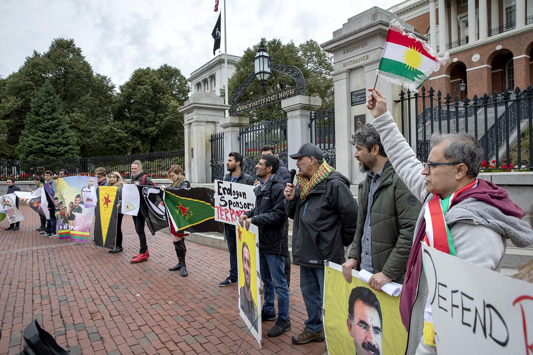 Protesters at a rally organized by two New England Kurdish associations chant and wave banners in front of the Massachusetts State House. (Robin Lubbock/WBUR)