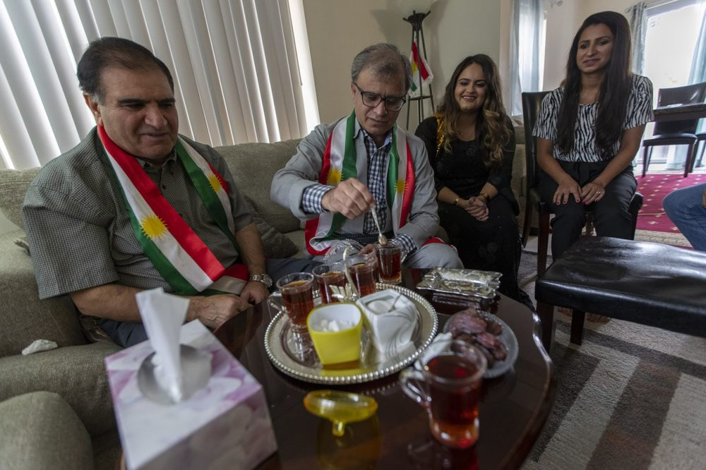 Omar Osman Omer, son Delshad Osman, and daughters Shawnam and Ala Osman, enjoy afternoon tea in their home in Dorchester. (Jesse Costa/WBUR)