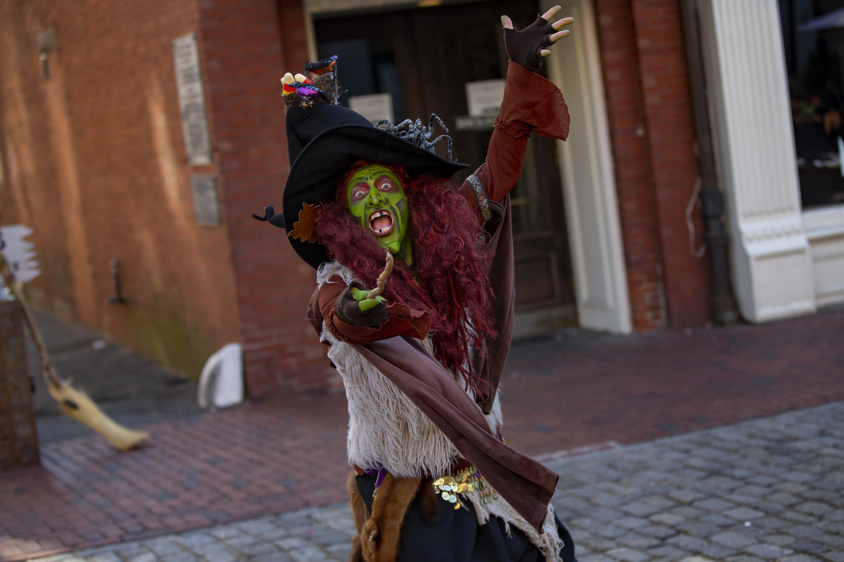 Street performer Borah Brewington Snaggletooth XIII, aka Brian Sims, casts a spell on Essex Street. (Jesse Costa/WBUR)