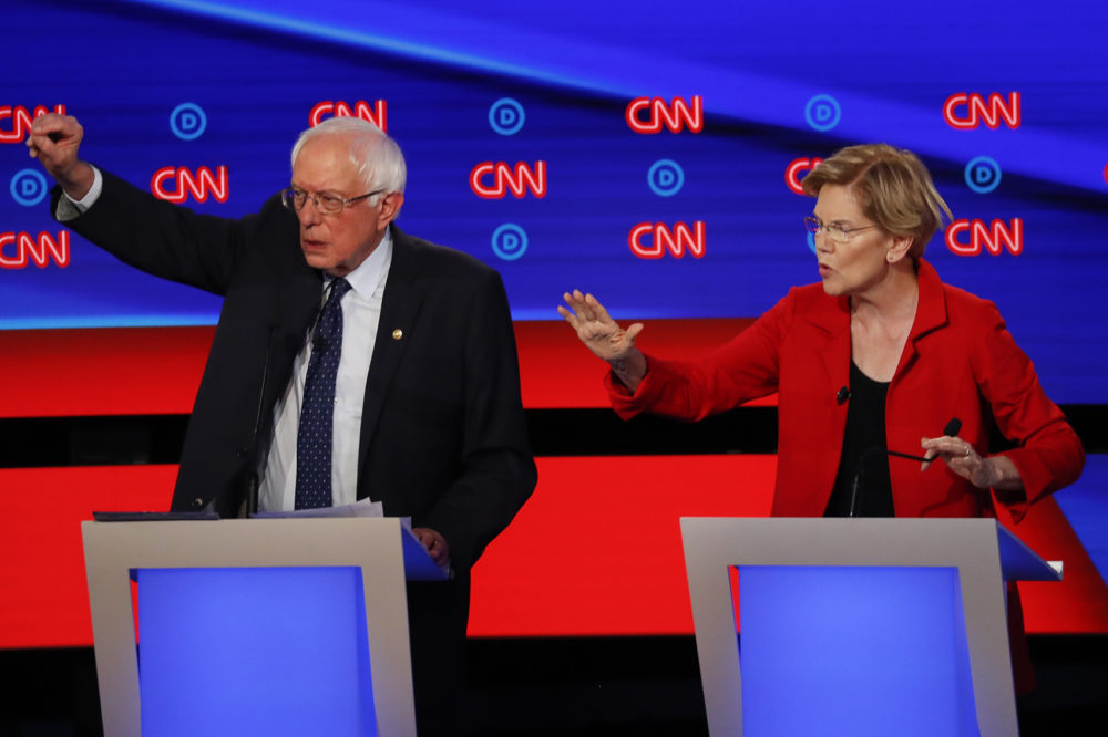 A CBS poll has Sen. Bernie Sanders, I-Vt., leading in both Iowa and New Hampshire ahead of next month's Democratic presidential primaries while Sen. Elizabeth Warren, D-Mass., lags behind. Here, Sanders and Warren talk during in the first of two Democratic presidential primary debates hosted by CNN last July. (Paul Sancya/AP)
