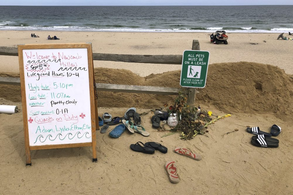 A sign informs visitors of lifeguard hours at Newcomb Hollow Beach in Wellfleet, Mass. Arthur Medici of Revere, Mass., died after being bitten by a shark offshore there on Sept. 15, 2018. (Susan Haigh/AP)