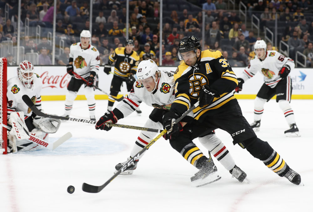 Boston Bruins' Patrice Bergeron tries to hold off Chicago Blackhawks' Adam Boqvist during the first period of an NHL preseason hockey game, Sept. 28, 2019, in Boston. (Winslow Townson/AP)