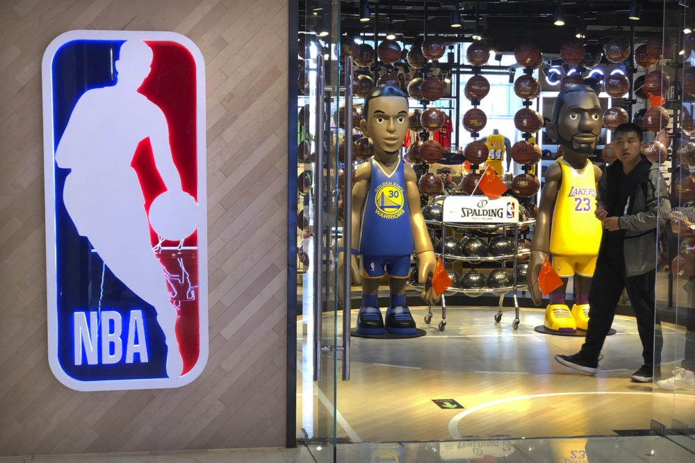 A man walks past statues of NBA players Stephen Curry of the Golden State Warriors, left, and Lebron James of the Los Angeles Lakers holding Chinese flags in the entrance of an NBA merchandise store in Beijing, Tuesday, Oct. 8, 2019. (Mark Schiefelbein/AP)