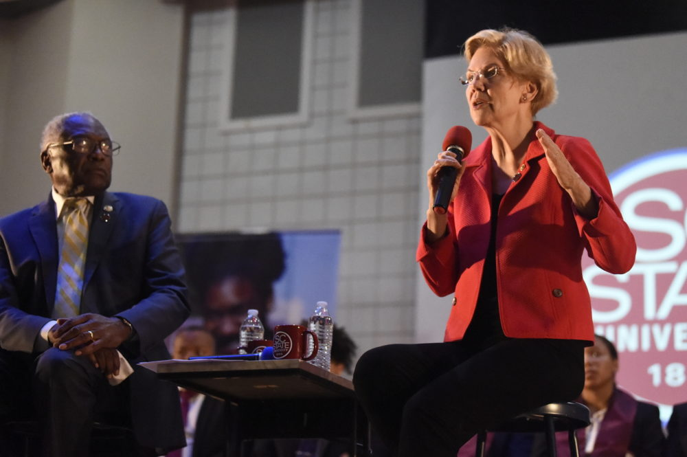 U.S. House Majority Whip Jim Clyburn, left, watches as U.S. Sen. Elizabeth Warren speaks at a town hall about their joint legislative effort on student debt loan relief on Wednesday at South Carolina State University in Orangeburg, S.C. (Meg Kinnard/AP)