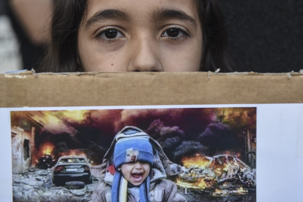 A Kurdish girl looks on as she holds a picture during a protest in the northern city of Thessaloniki, Greece, on Thursday. Oct. 17, 2019. (Giannis Papanikos/AP)