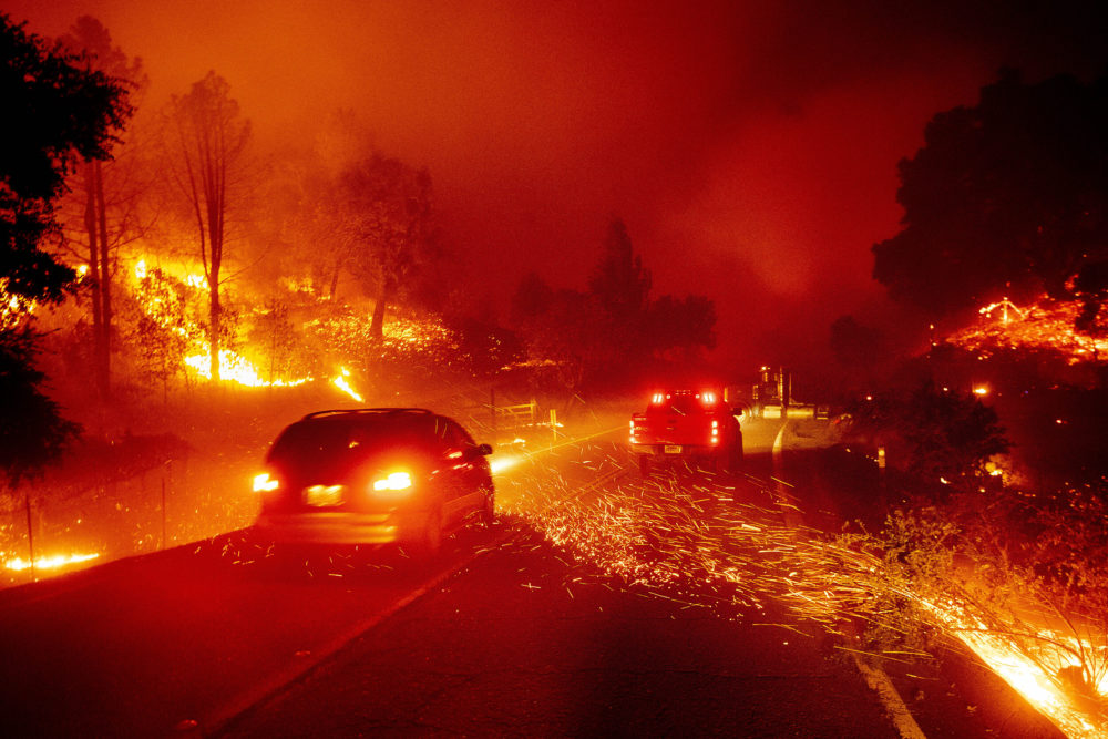 Embers fly across a roadway as the Kincade Fire burns through the Jimtown community of Sonoma County, Calif., on Thursday. (Noah Berger/AP)