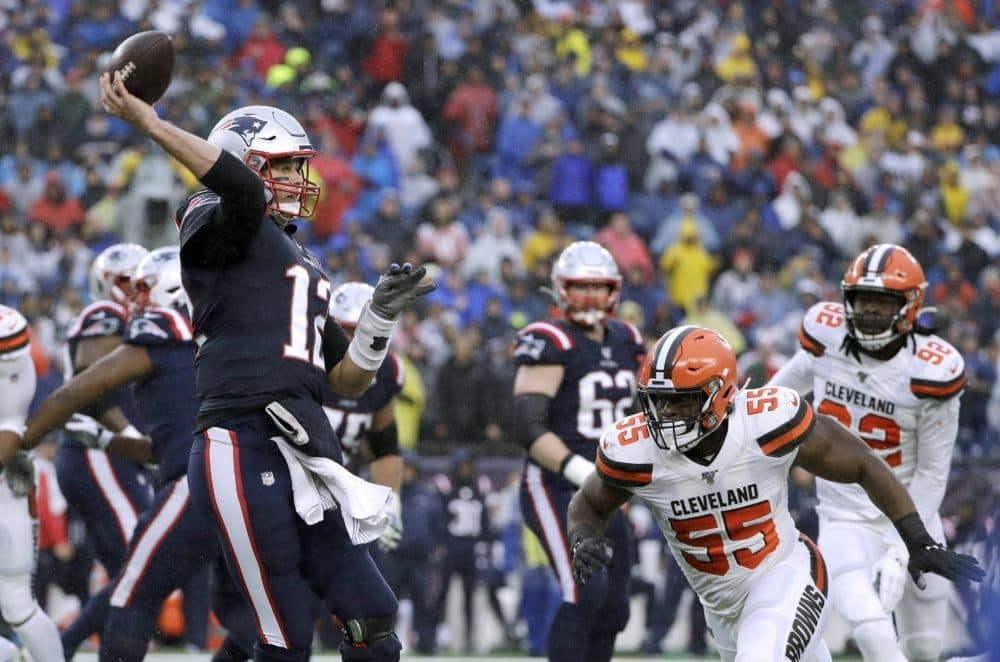 Patriots quarterback Tom Brady passes under pressure from Browns linebacker Genard Avery (55) in the first half of the game. (Steven Senne/AP)