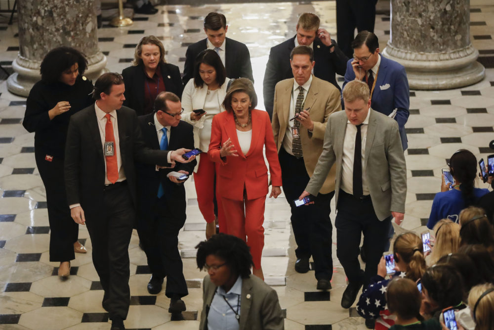House Speaker Nancy Pelosi of Calif., center, is followed by members of media as she leaves the House Chamber after announcing that the House votes 232-196 to pass resolution on impeachment procedure to move forward into the next phase of the impeachment inquiry into President Trump on Capitol Hill in Washington, Thursday, Oct. 31, 2019. The resolution would authorize the next stage of impeachment inquiry into President Donald Trump, including establishing the format for open hearings, giving the House Committee on the Judiciary the final recommendation on impeachment, and allowing President Trump and his lawyers to attend events and question witnesses. (AP Photo/Pablo Martinez Monsivais)