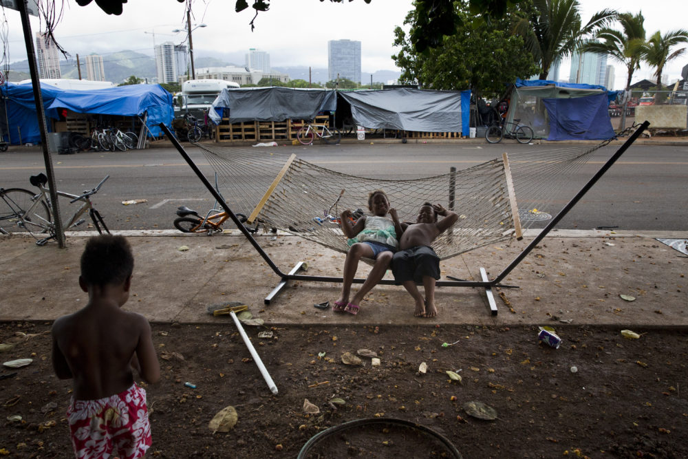 In this 2015 photo, two children rest on a hammock at a homeless encampment in the Kakaako district of Honolulu. Homelessness in Hawaii has grown in recent years, leaving the state with 487 homeless per 100,000 people, the nation's highest rate per capita, according to federal statistics. (Jae C. Hong/AP)