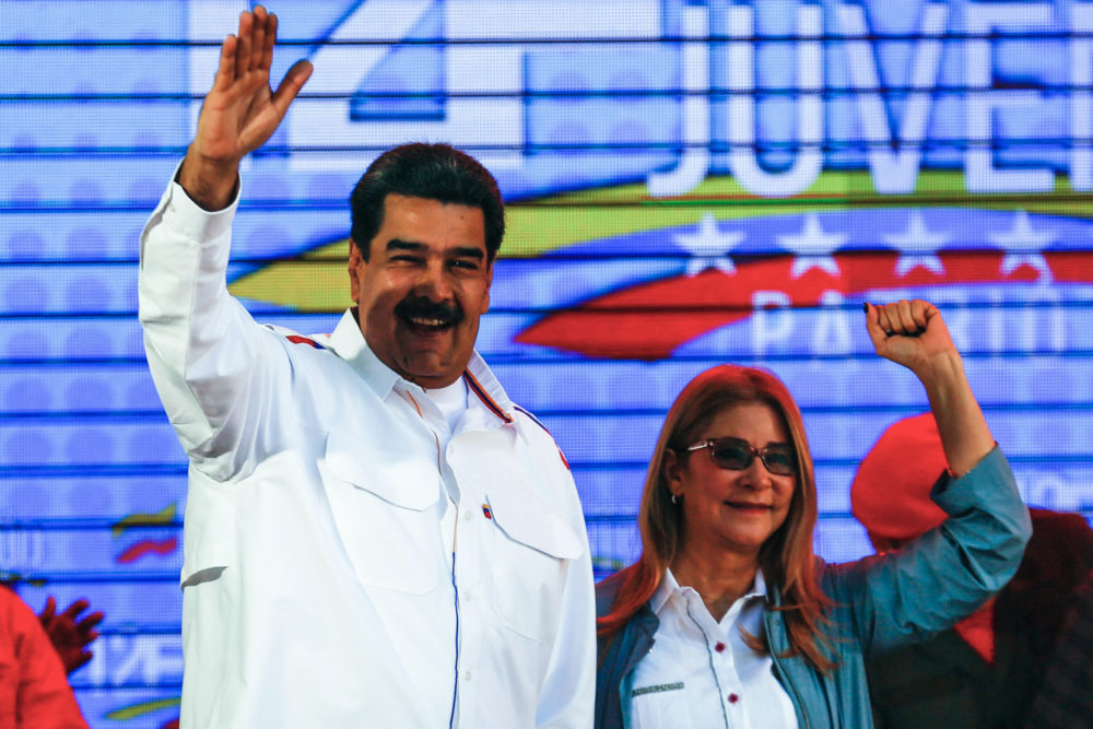 "Nicolas Maduro and his wife Cilia Flores wave during celebrations in the framework of the ""Youth Day"" at the Bolivar Square in Caracas, Venezuela, on Feb. 12, 2019. (Orangel Hernandez/AFP/Getty Images)"