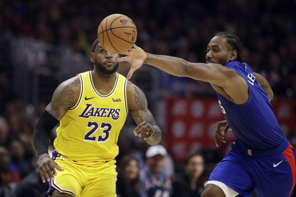 Kawhi Leonard (right) steals the ball during Tuesday's Clippers-Lakers game. (Marcio Jose Sanchez/AP)