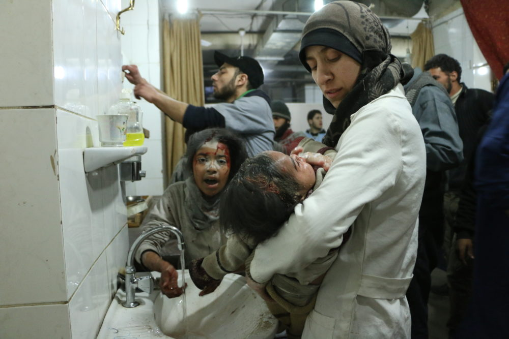 Dr. Amani (R) treats an injured baby among other medical staff and victims in Al Ghouta, Syria. (National Geographic)