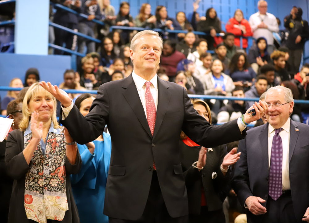 Gov. Charlie Baker gestures to the audience in the gymnasium of Boston's English High School after signing a landmark education funding reform law on Tuesday. (Sam Doran/SHNS)
