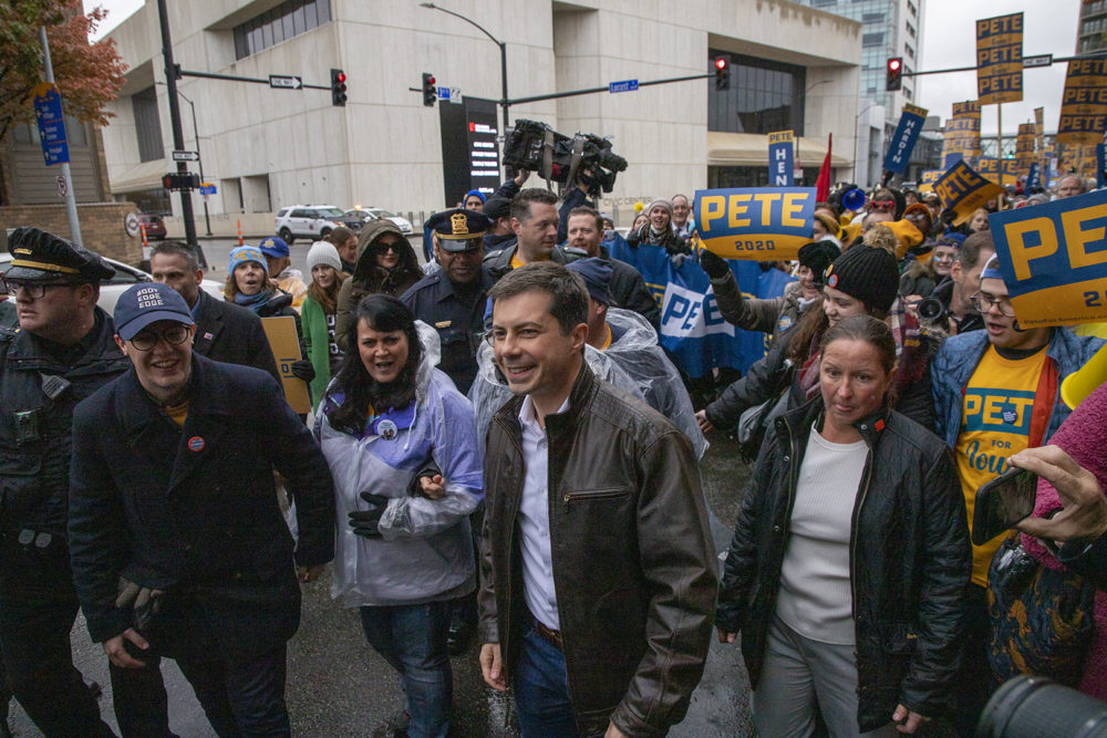 South Bend, Indiana Mayor Pete Buttigieg marches down a street in Des Moines, Iowa, with supporters before the Liberty and Justice Celebration on November 1, 2019. (Clay Masters/Iowa Public Radio)