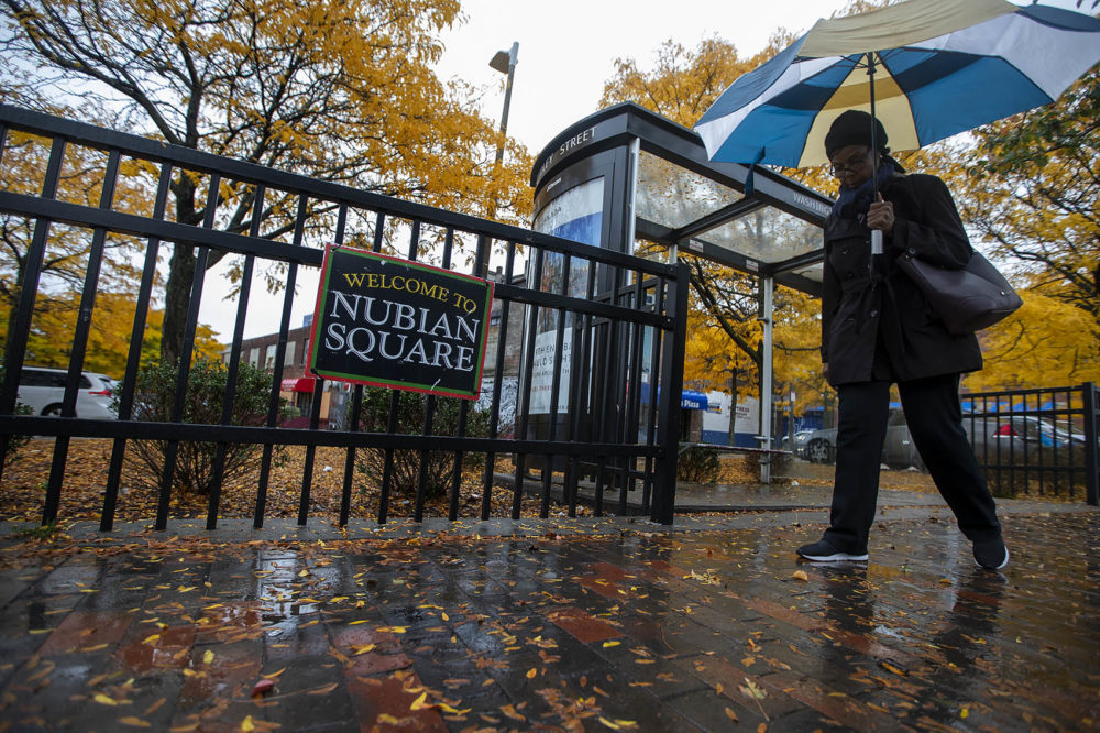 """A woman walks past a """"Welcome to Nubian Square"""" sign at the gate of the Dudley Square Plaza on Washington St. (Jesse Costa/WBUR)"""