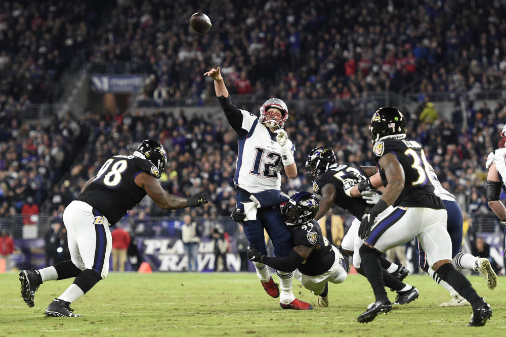 New England Patriots quarterback Tom Brady attempts a pass as Baltimore Ravens linebacker Matthew Judon makes a hit during the first half of an NFL football game Sunday in Baltimore. (Gail Burton/AP)