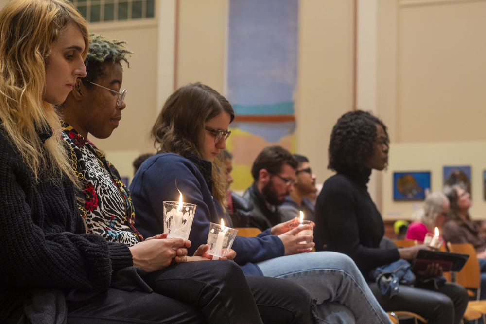 Participants hold candles during the Transgender Day of Remembrance gathering at the Cathedral of Saint Paul on Sunday. (Quincy Walters/WBUR)