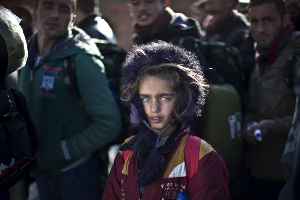 In this Dec. 5, 2015 file photo, Yazidi refugee Salma Bakir, 9, from Iraq, waits with her family to be permitted by Macedonian police to board a train heading to the Serbian border, near the southern Macedonian town of Gevgelija. (Muhammed Muheisen/AP)