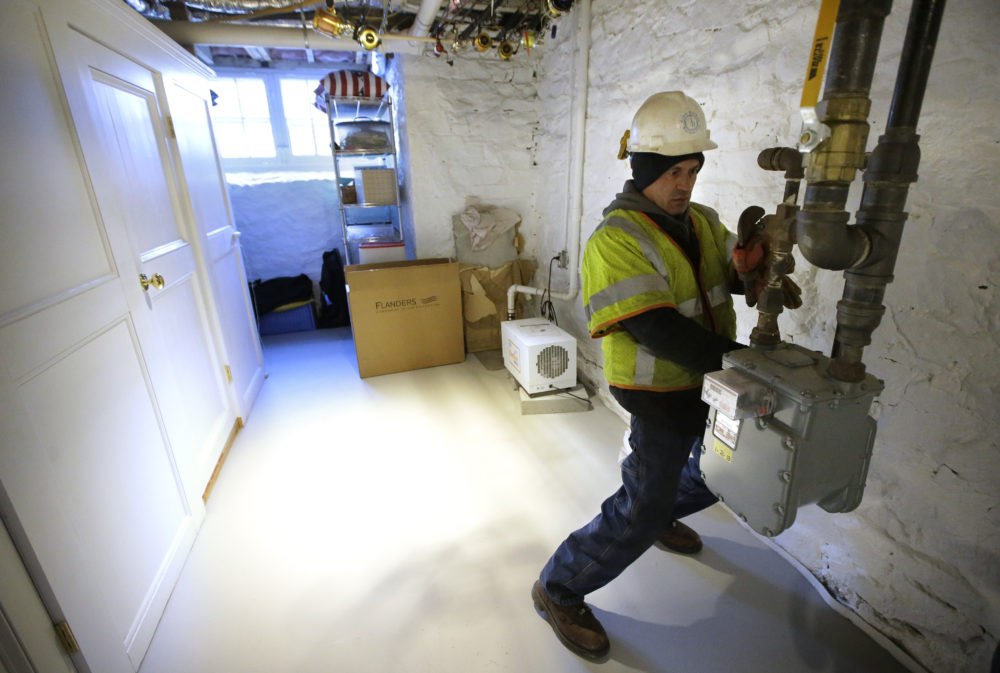 Joe Cabral, a sub-contractor for National Grid, uses a wrench to turn off the main natural gas line to a home, Tuesday, Jan. 22, 2019, in Newport, R.I. (Steven Senne/AP)