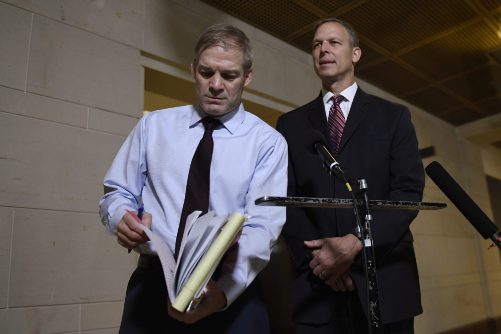 Rep. Jim Jordan, R-Ohio, left, looks for something in his notes as he and, Rep. Scott Perry, R-Pa., right, speak to reporters on Capitol Hill in Washington on Nov. 6 near the area where the interviews for the impeachment inquiry are being held. (Susan Walsh/AP)