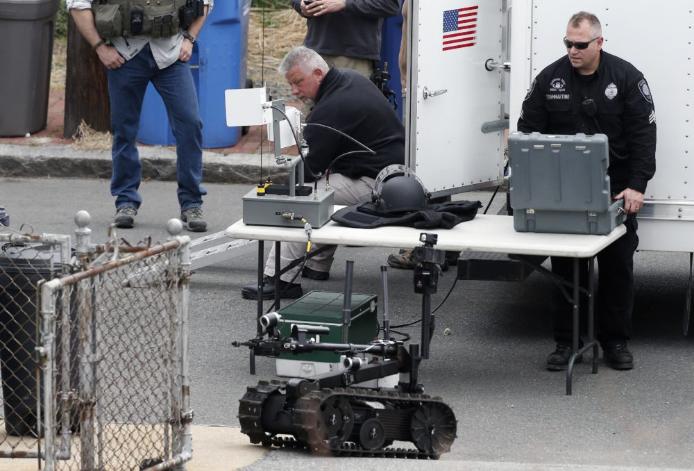Robots and police departments are no strangers. In this photo, a member of the Cambridge police bomb squad used a robot during a search for the Boston Marathon bombings suspect in 2013. (Michael Dwyer/AP)