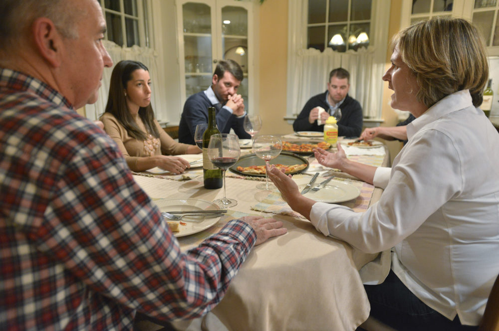 Anne Brennan, right, of Hingham Mass., speaks as, from left, brother-in-law Steve Marshall, of Hingham, niece Rebecca Malone, and her husband Brian Malone, both of Duxbury, Mass., and nephew Andrew Marshall, of Quincy, Mass., are gathered for dinner in Hingham, Mass., where politics are a frequent, and divisive topic of conversation. (Josh Reynolds/AP)