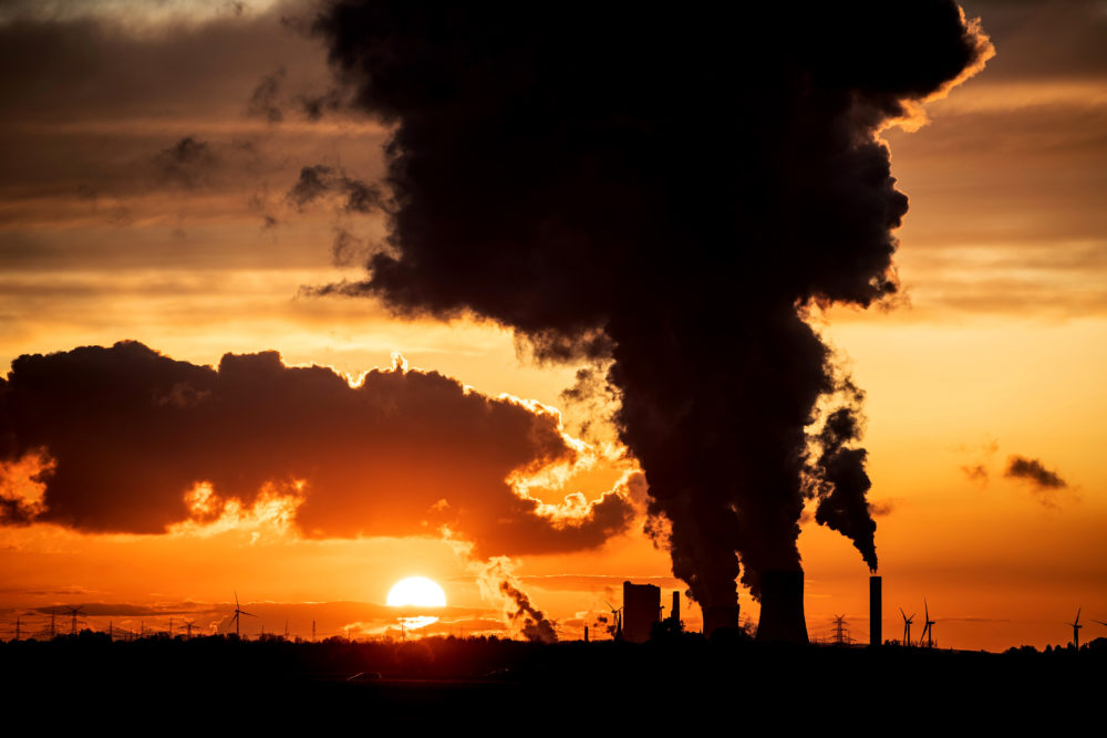 The sunset is pictured as steam rises from the chimneys of Niederaussen lignite-fired power plant in Roggendorf, western Germany on Nov. 8, 2019. (Federico Gambarini/dpa/AFP via Getty Images)