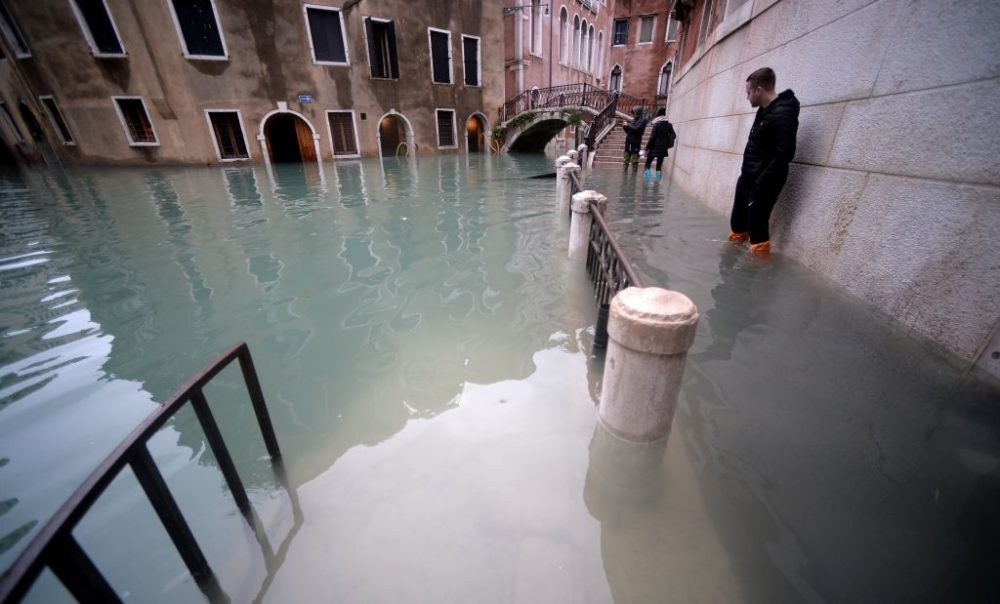 People stand in flooded Venice streets. (Filippo Monteforte/AFP/Getty Images)