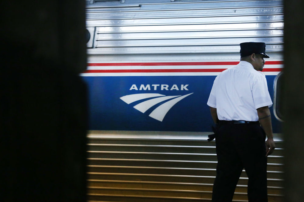 A train conductor stands next to an Amtrak train at New York's Pennsylvania Station. (Spencer Platt/Getty Images)