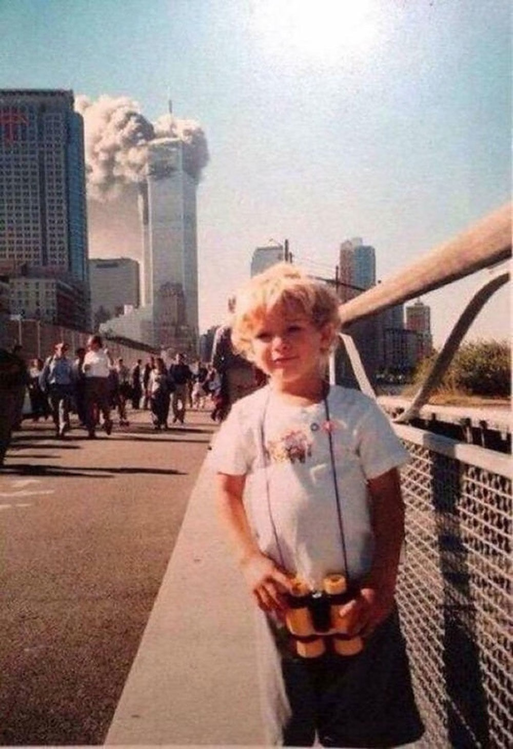 A frequently circulated viral photo, which shows a smiling kid in front of one of the burning World Trade Center towers (courtesy Underunderstood)