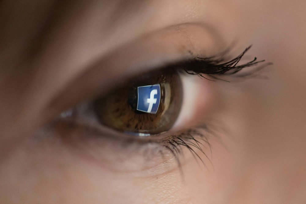An illustration picture taken on March 22, 2018 in Paris shows a close-up of the Facebook logo in the eye of an AFP staff member posing while she looks at a flipped logo of Facebook. (CHRISTOPHE SIMON/AFP via Getty Images)