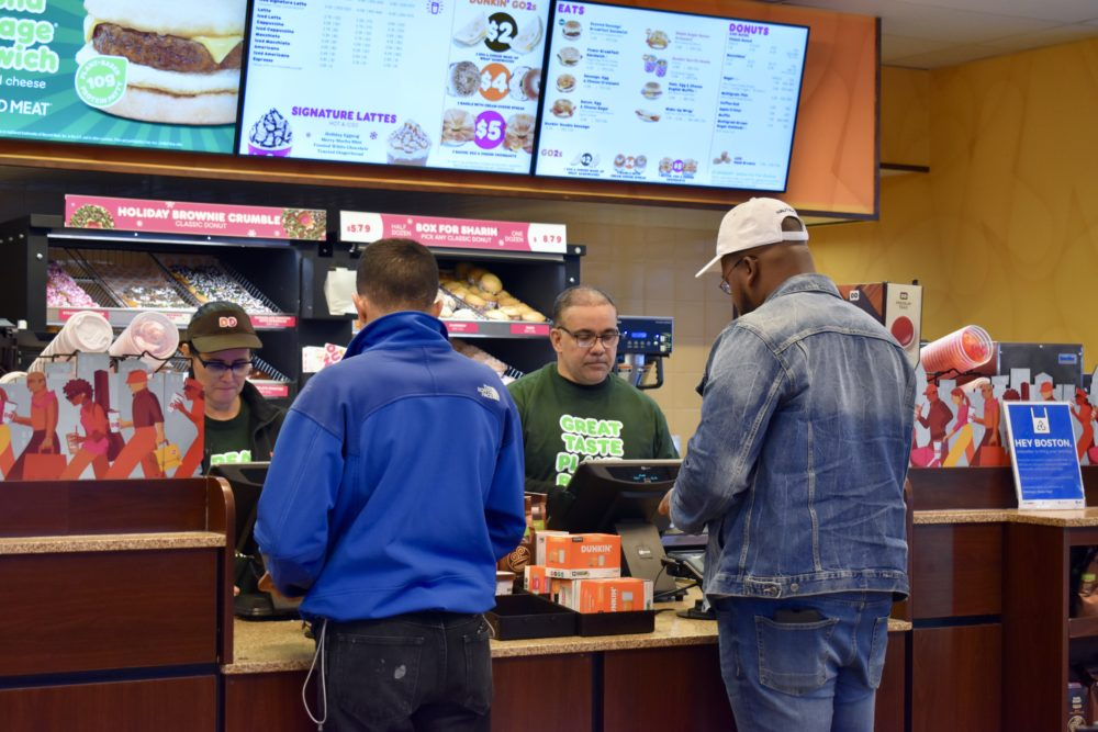 At the Dunkin' on North Beacon Street in Brighton, Nehemiah Campos, right, and another employee take orders. (Meghan B. Kelly/WBUR)