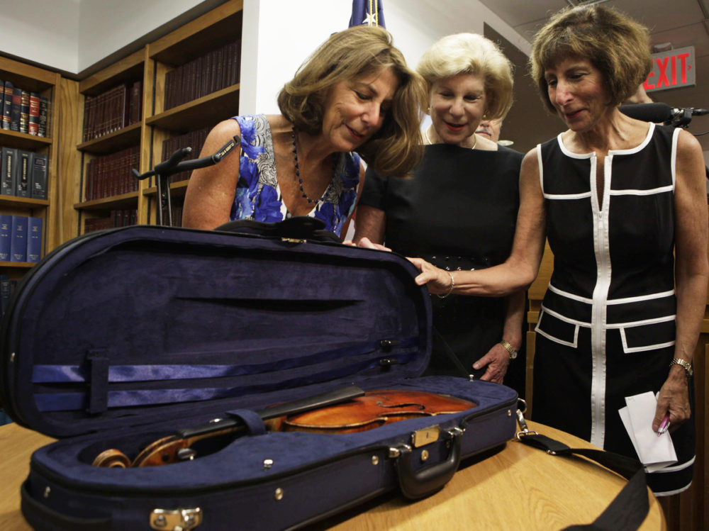 The Totenberg sisters — Amy (from left), Nina and Jill —€ see their father's stolen Stradivarius for the first time in 35 years at the U.S. attorney's office in New York City on Thursday. (Lydia Thompson/NPR)
