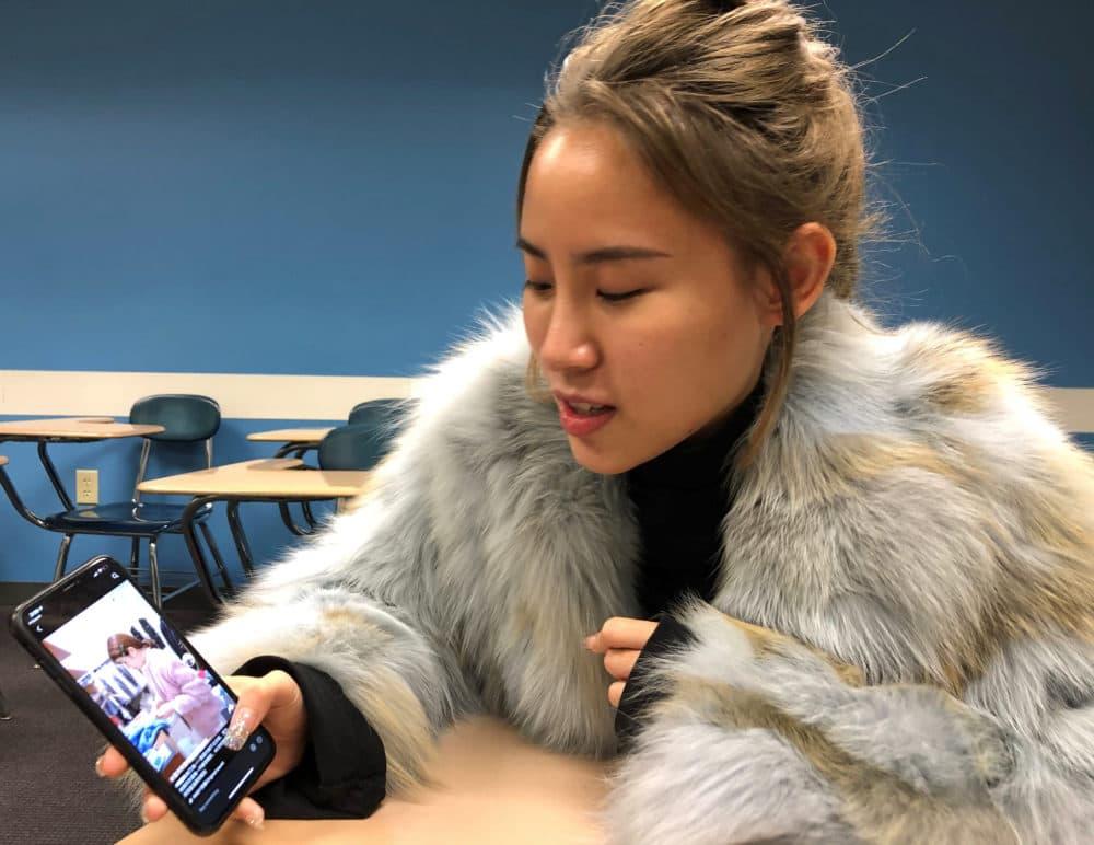 Xiwen Zheng browses fashion discounts between classes at Boston University's Center for English Language & Orientation Programs. (Callum Borchers/WBUR)