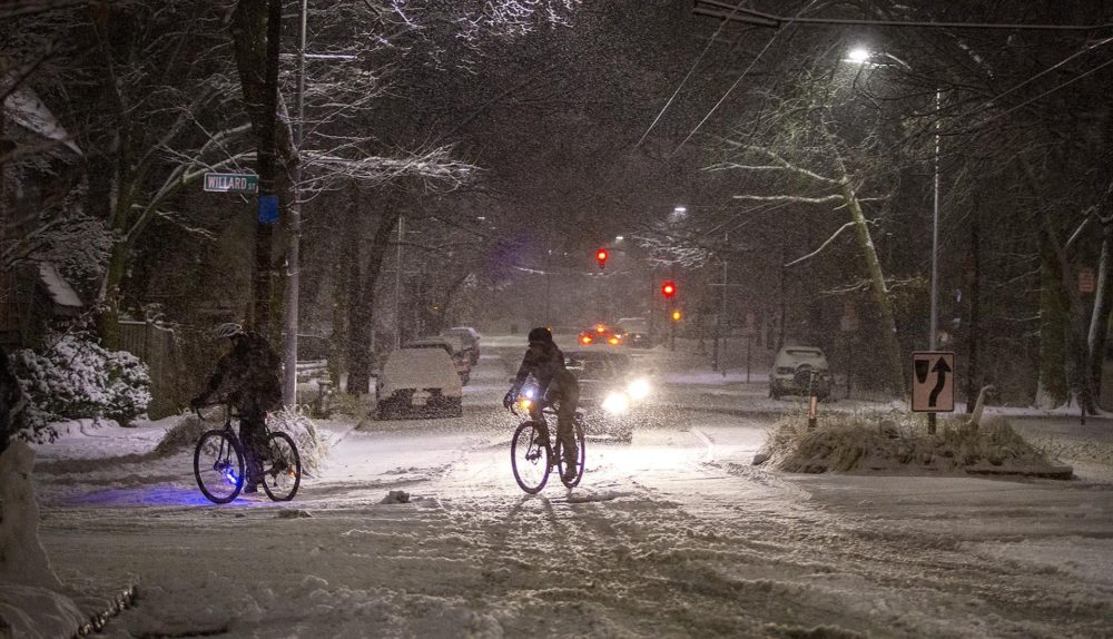 Bicyclists make a turn off a snowy Mount Auburn Street on Sunday evening. (Robin Lubbock/WBUR)