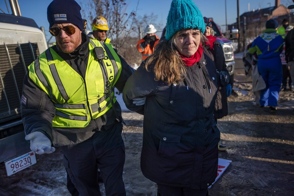 Weymouth Police officers arrest Lisa Jennings during a protest outside of the natural gas compressor construction site. (Jesse Costa/WBUR)